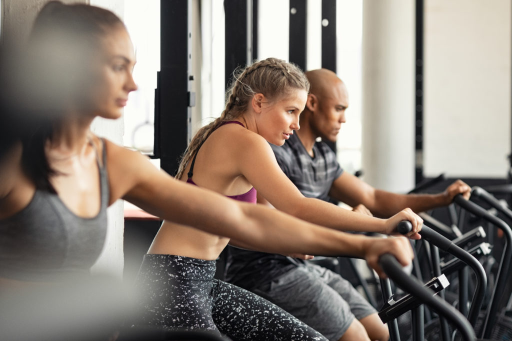 Group of determined multiethnic people at gym exercising on stationary bike. Concentrated fitness woman training on exercise bike with class. Man and women behind riding cycling machine in hard efforts at gym.