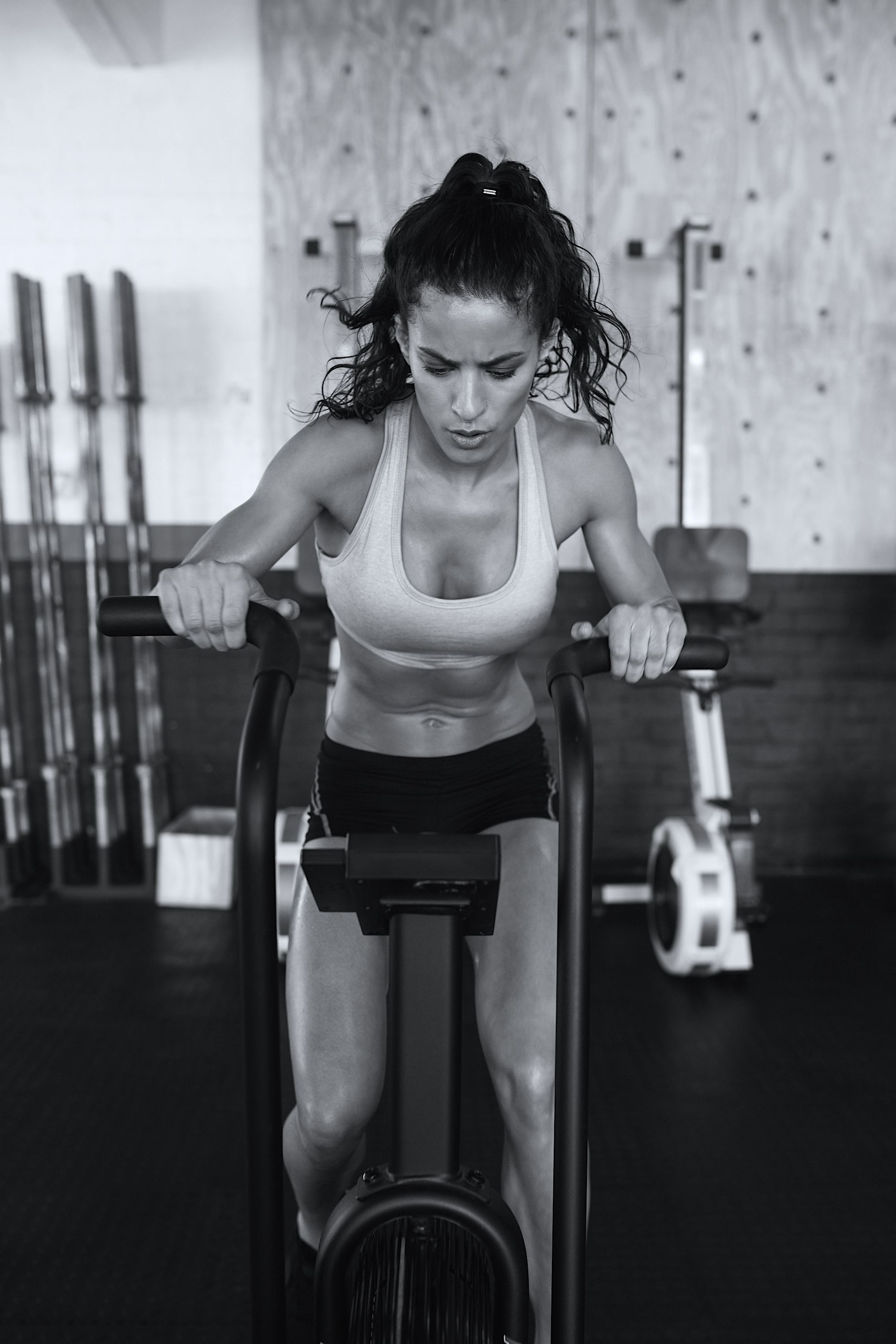Fitness woman on bicycle doing cardio workout at gym. Fit young female exercising on gym bike.